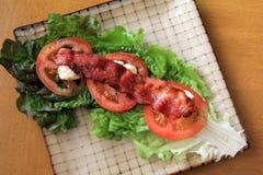 Placa modelada con lechuga de hoja roja, los tomates frescos, cortados y el tocino curruscante en el top Fotos de archivo