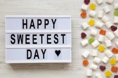 Placa moderna com palavra a mais doce feliz do ` do dia do ` e doces em um fundo de madeira branco, vista aérea Vista superior, c foto de stock royalty free