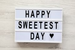 Placa moderna com palavra a mais doce feliz do ` do dia do ` do texto sobre a superfície de madeira branca, vista superior De cim fotos de stock