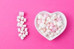 Placa na forma do coração com um marshmallow em um fundo cor-de-rosa fotografia de stock