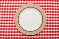 A placa na tabela de madeira com vermelho verificou a toalha de mesa Fotografia de Stock Royalty Free