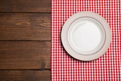 A placa na tabela de madeira com vermelho verificou a toalha de mesa Fotografia de Stock