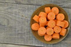 Placa negra con las zanahorias cortadas densamente en el fondo de madera, la derecha Imagenes de archivo