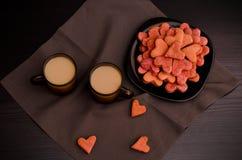 Placa negra de las galletas con en forma de corazón, dos tazas de café, el día de tarjeta del día de San Valentín Fotos de archivo libres de regalías