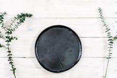 Placa negra vacía de la visión superior en la madera imágenes de archivo libres de regalías