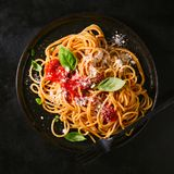 Placa oscura con espaguetis italianos en oscuridad Foto de archivo libre de regalías