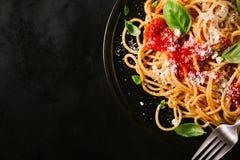 Placa oscura con espaguetis italianos en oscuridad Imagen de archivo libre de regalías