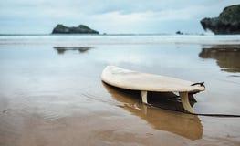Placa para surfar na praia abandonada do oceano Imagens de Stock Royalty Free