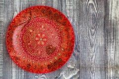 Placa pintado à mão vermelha da vista superior na superfície de madeira imagem de stock