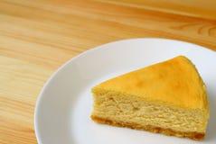 A placa planície amarela cremosa mouthwatering do bolo de queijo cozido serviu na tabela de madeira imagem de stock royalty free