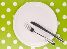 Placa plana blanca vacía con la bifurcación y el cuchillo Imagen de archivo libre de regalías