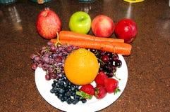 Placa por completo de frutas y de beries maduros en fondo marrón del granito imagen de archivo libre de regalías