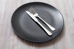 Placa preta com faca paralela, colher no cinza Fotos de Stock Royalty Free