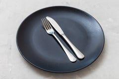 Placa preta com faca paralela, colher no concreto Imagem de Stock Royalty Free
