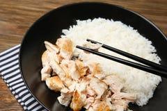 Placa preta com galinha e arroz deliciosos Fotos de Stock Royalty Free