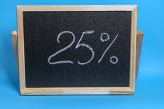 Placa preta em um quadro de madeira em um fundo azul com a inscri??o 25 por cento Modelo para comprar, vendas imagem de stock