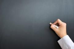 Placa preta vazia com mão e giz Imagem de Stock