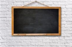 Placa preta vazia na parede de tijolo branca Imagens de Stock