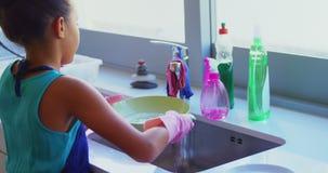 Placa que se lava de la niña linda en el fregadero de cocina 4k almacen de metraje de vídeo