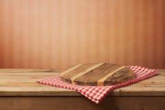 Placa redonda de madeira vazia na toalha de mesa sobre o fundo vermelho da parede para a montagem do produto fotos de stock