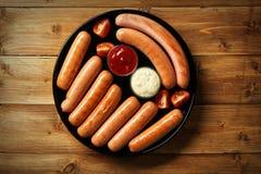 Placa redonda negra con las salchichas y las salsas asadas a la parrilla deliciosas en la tabla de madera Fotografía de archivo libre de regalías