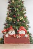 Placa roja adornada y borrosa del andt del árbol de navidad con el muñeco de nieve imagen de archivo libre de regalías