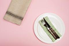 Placa vacía blanca con la servilleta del cuchillo y de la materia textil de la bifurcación en fondo rosado fotografía de archivo libre de regalías