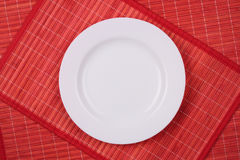 Placa vacía blanca en un rojo Imágenes de archivo libres de regalías