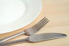 Placa vacía con el cuchillo y bifurcación en la tabla de madera Imagenes de archivo