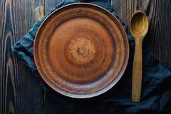 Placa vacía de la arcilla y cuchara de madera en la opinión superior del fondo de madera imagen de archivo libre de regalías