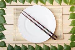 Placa vacía en una estera de bambú con los palillos, opinión superior, sobre un fondo de madera, enmarcado con las hojas de un ár Fotos de archivo