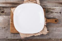 Placa vacía ligera con los accesorios de la cocina en un fondo de madera en estilo del vintage Visi?n desde arriba imagen de archivo