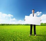 Placa vazia do whith do homem de negócio à disposição no campo da grama Imagens de Stock Royalty Free