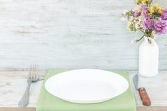 Placa vazia na toalha de mesa ou guardanapo na tabela de madeira sobre o fundo do cimento fotografia de stock