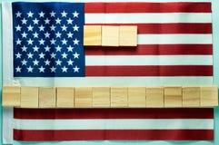 Placa vazia para a inscrição em quinze cubos de madeira apresentada na bandeira americana no fundo azul foto de stock