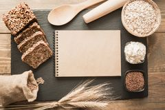 Placa vazia para uma receita do pão com ingredientes, farinha, trigo, pão, centeio, sementes de linho ao redor no prato preto da  imagem de stock