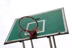 Placa verde velha do basquetebol com aro vermelha e da malha branco-vermelha no fundo branco do céu imagem de stock royalty free