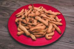 Placa vermelha completamente das cookies sobre uma tabela de madeira Fotografia de Stock Royalty Free