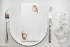 Placa y cubiertos en la tabla en restaurante Imagenes de archivo
