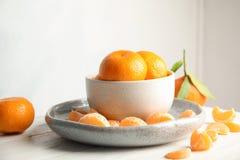 Placa y cuenco con las mandarinas maduras fotografía de archivo libre de regalías
