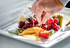 Placa y mano de la fruta que toman la invitación Foto de archivo