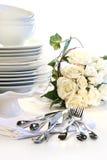 Placas blancas empiladas con los utensilios y las rosas Imagenes de archivo