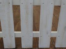 Placas brancas da cerca e assoalho de madeira marrom imagens de stock