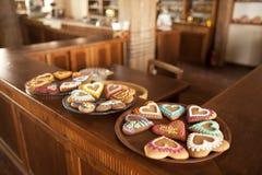 Placas com os corações do pão-de-espécie que estão em uma loja foto de stock
