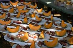 Placas com partes de melão e de jamon em bandejas de madeira para a distribuição no feriado local foto de stock royalty free