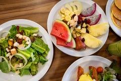 Placas com pratos suporte no aço, nas saladas, nas sobremesas e nos frutos fotos de stock