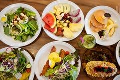 Placas com pratos suporte no a?o, nas saladas, nas sobremesas e nos frutos imagem de stock royalty free
