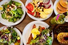 Placas com pratos suporte no a?o, nas saladas, nas sobremesas e nos frutos fotografia de stock royalty free