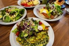 Placas com pratos suporte no a?o, nas saladas, nas sobremesas e nos frutos imagem de stock