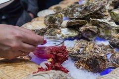 Placas con las ostras en las manos de visitantes imágenes de archivo libres de regalías